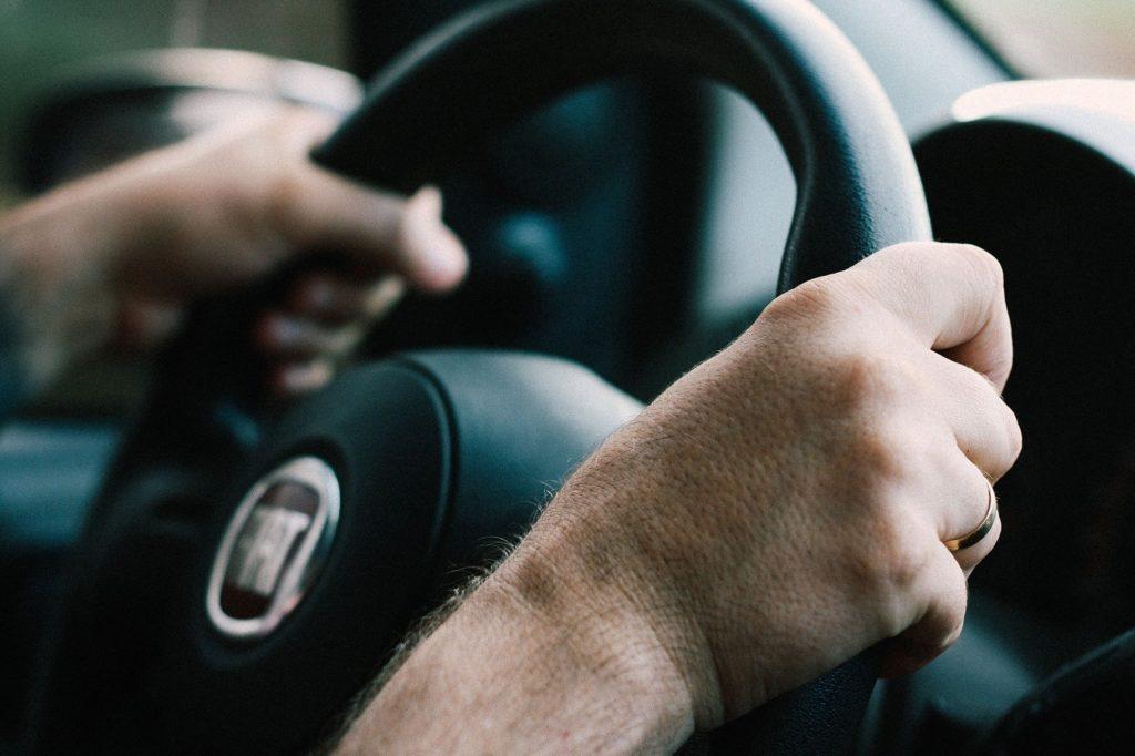 Hombre sujetado un volante de un coche